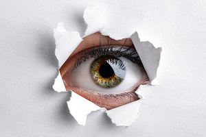 bigstock-Womans-eye-peeking-through-a-h-52524373